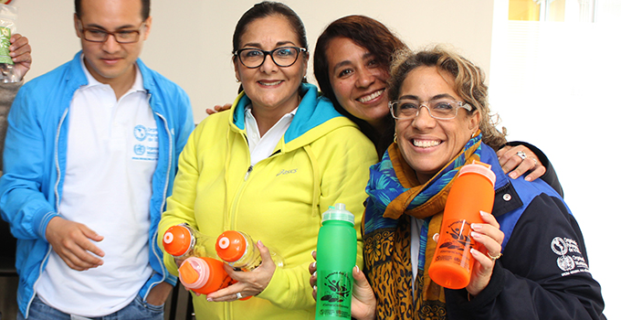Photo of a group of women smiling and holding water bottles