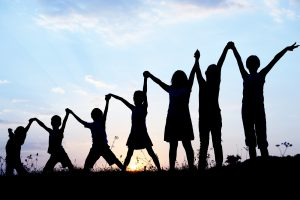 Photo of children in silhouette against a sky, holding raised hands on a hillside.